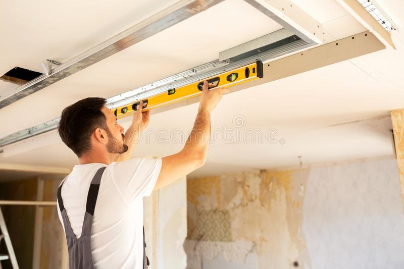 House renovation worker checking the alignment of a ceiling stock image