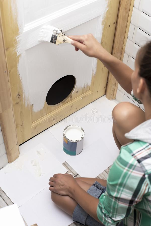 House repair. Woman sitting on the floor in the bathroom and paint wooden door with a round entrance for cats in white color with. House repair. Cute woman stock images