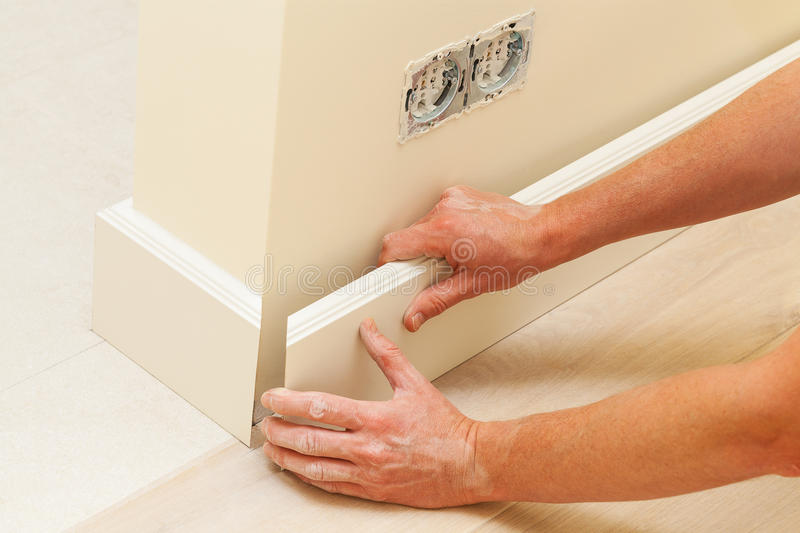 House repairing, skirting board. Putting skirting board to a fresh paint wall stock photos
