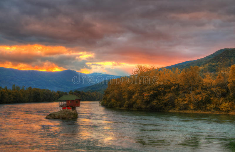 House in river Drina near Bajina Basta, Western Serbia. Amazing autumn picture with lights, beautiful warm colors, house on the rock in river Drina and sunset stock images