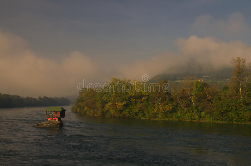 House in river Drina near Bajina Basta, Western Serbia. Amazing autumn picture with morning light, beautiful warm colors, house on the rock in river Drina and royalty free stock image
