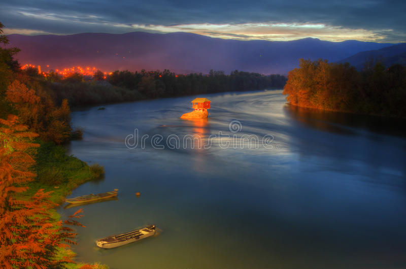House in river Drina near Bajina Basta, Western Serbia. Amazing night picture with lights, beautiful soft colors, house on the rock in river Drina, sunset in royalty free stock images