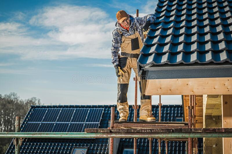 House Roof Construction. Ceramic Tiles House Roof Construction. Contractor Worker on Scaffolding Taking Last Look on the Finished Rooftop. Roofing Industry royalty free stock image