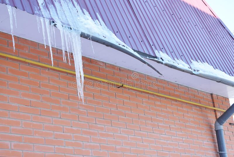 House Roof Gutter damaged by ice and heavy wet snow. Broken house roof top gutter pipeline by icicles royalty free stock photography