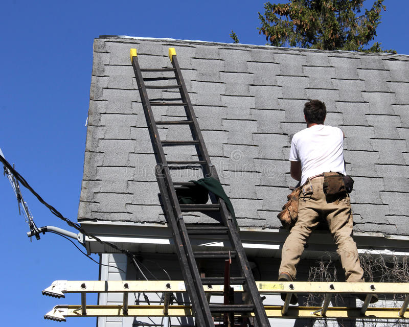 House roof repair. Carpenter on a ladder repairing the roof of a house stock image