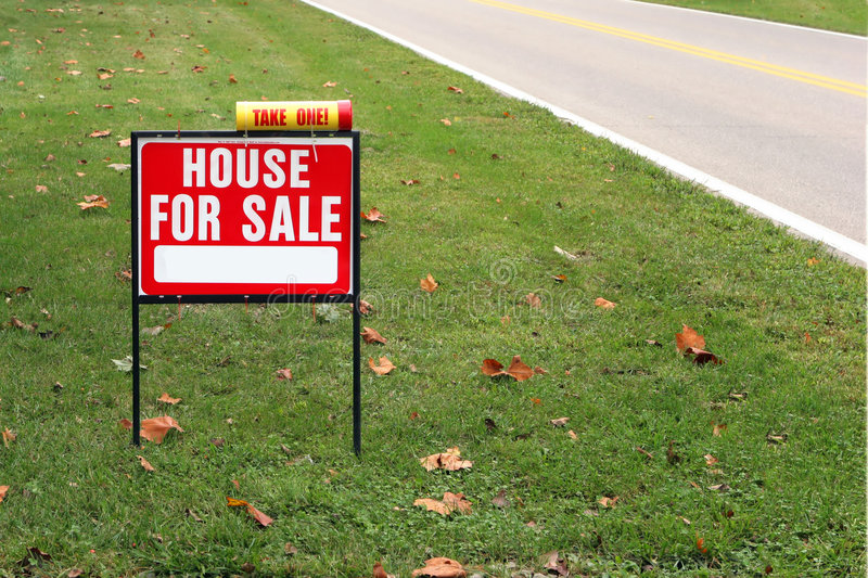 House for sale. Sign in grass by a road royalty free stock photos