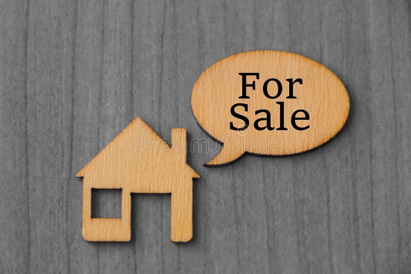 House for sale. Concept of House for sale with wooden house and wooden sign stock photos