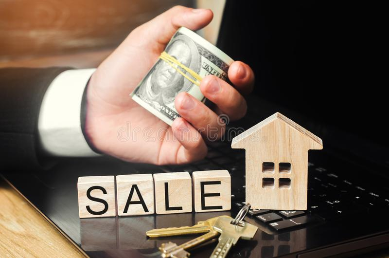 House sale online. concept of real estate. model of the house, keys, dollars and the inscription. `sale` on wooden blocks. apartment. services of a realtor stock image