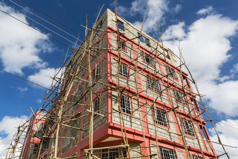 House With Scaffolding in Nairobi, Kenya. A small appartment building under construction with typical local scaffolding in the village of Tassia in Nairobi stock image