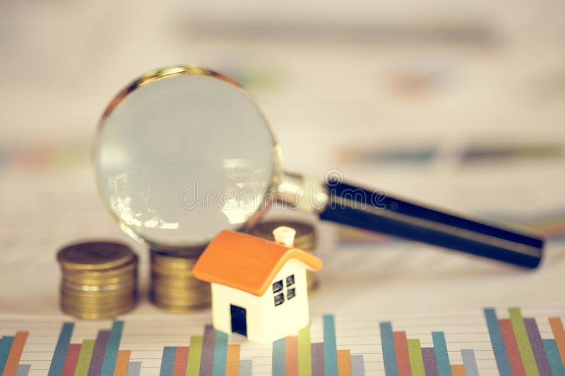 House searching concept with a magnifying glass, house and money. magnifying glass and coins. concept of mortgage, construction, royalty free stock photo