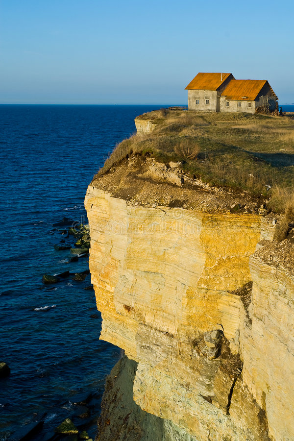 House on seaside cliff. A late afternoon view of a small house built on the edge of a vertical cliff overlooking the Baltic sea at Paldiski, Estonia royalty free stock photos