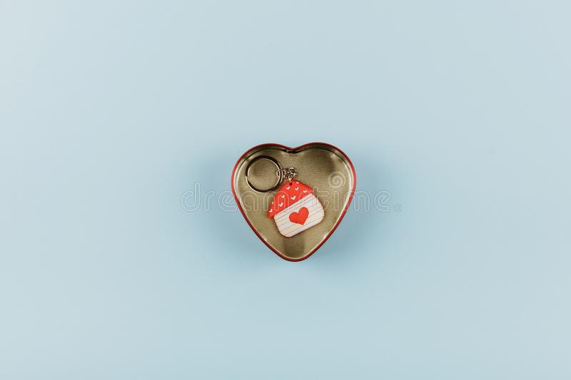 House shaped keychain with red heart in heart shaped metal box on blue background royalty free stock image