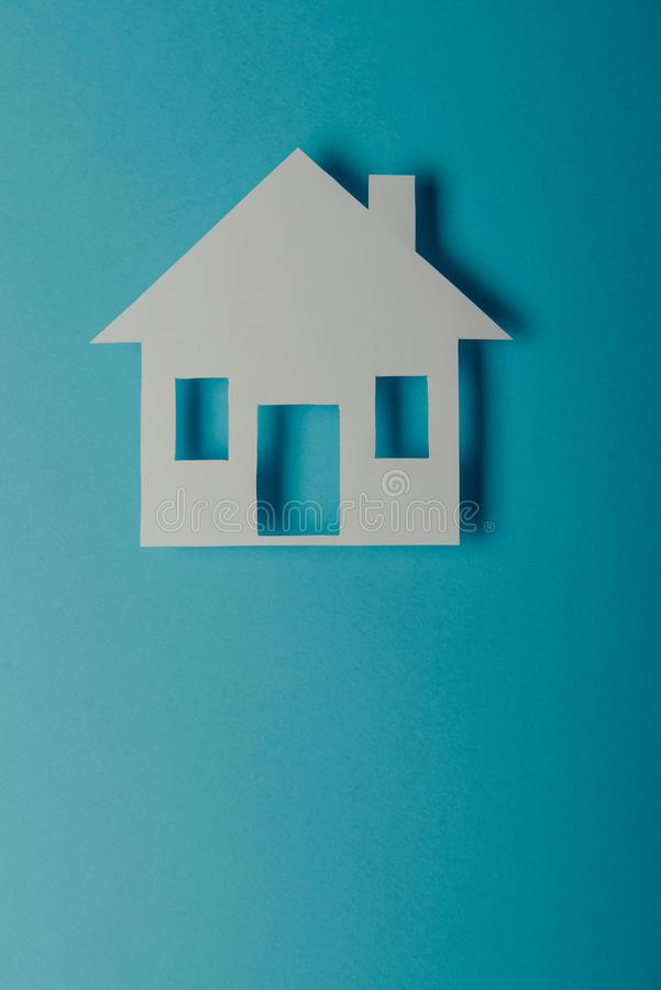 House shaped paper cutout. On on blue background, flat, concept, construction, dream, home, architecture, design, model, residential, white, close, green, image stock photo