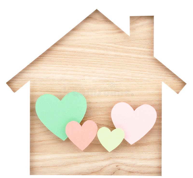 House shaped paper cutout and four hearts on natural wood lumber stock photos