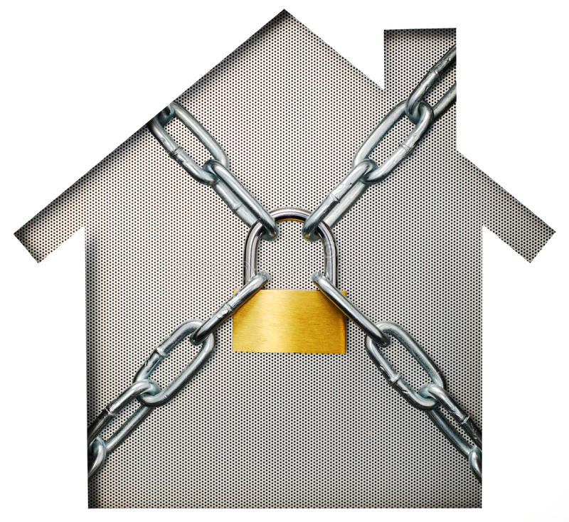 House shaped paper cutout and padlock on punching metal. stock photo