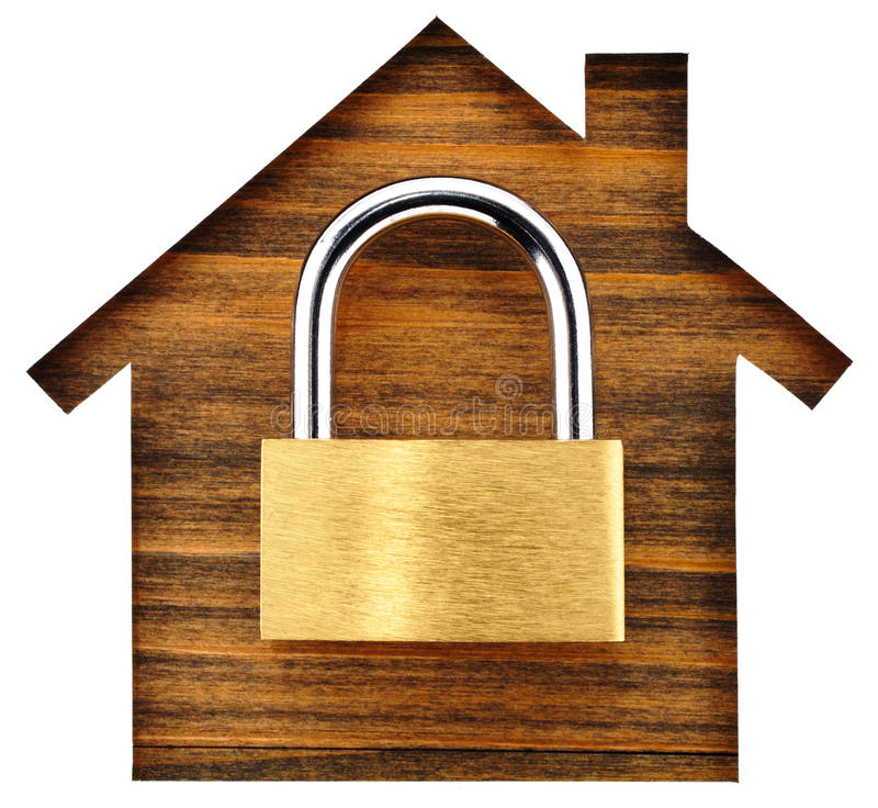 House shaped paper cutout and padlock on wood lumber. stock photography