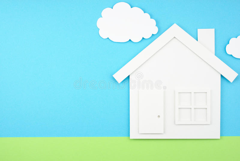 House shaped paper cutout on sky and grass field made of paper. stock photos