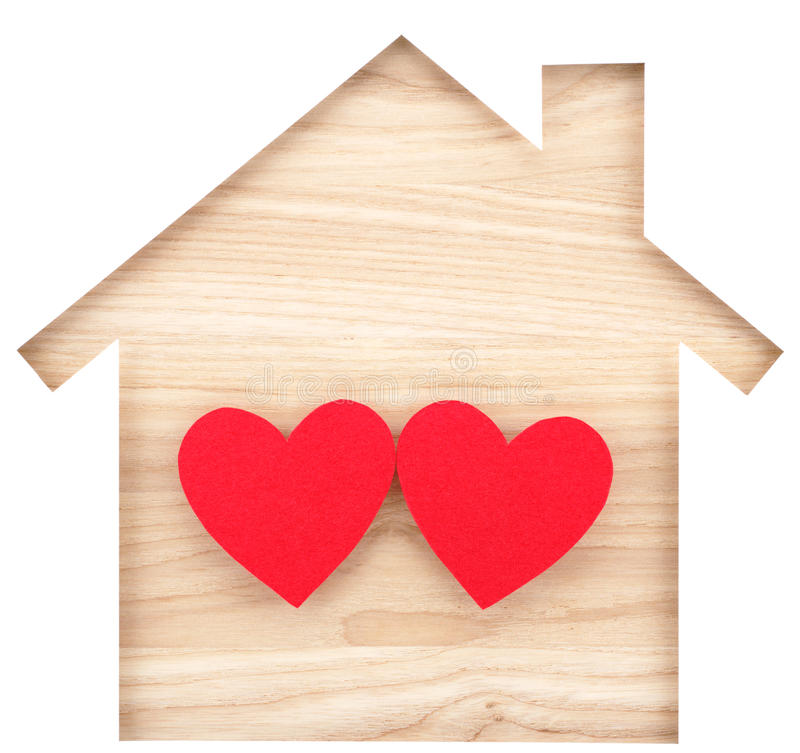 House shaped paper cutout and two hearts on natural wood lumber. stock photography
