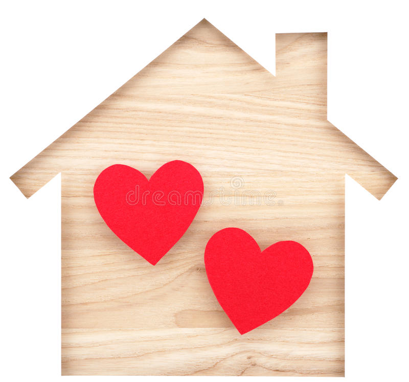 House shaped paper cutout and two hearts on natural wood lumber. royalty free stock photos