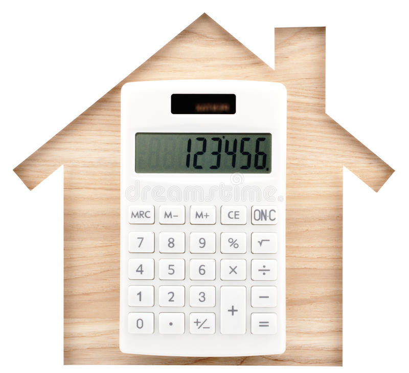 House shaped paper cutout and white calculator on natural wood l royalty free stock photo