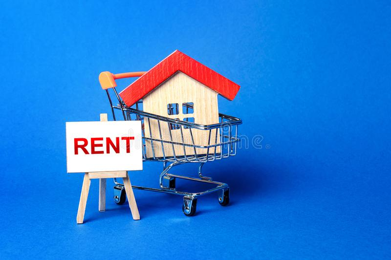 A house in a shopping cart and an easel with a word Rent. Rental housing and apartments, choice between buying and renting. Real estate prices and the stock photos