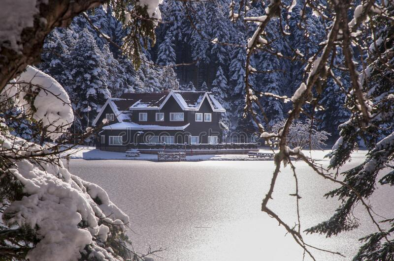 House at the shore of the frozen lake stock photography