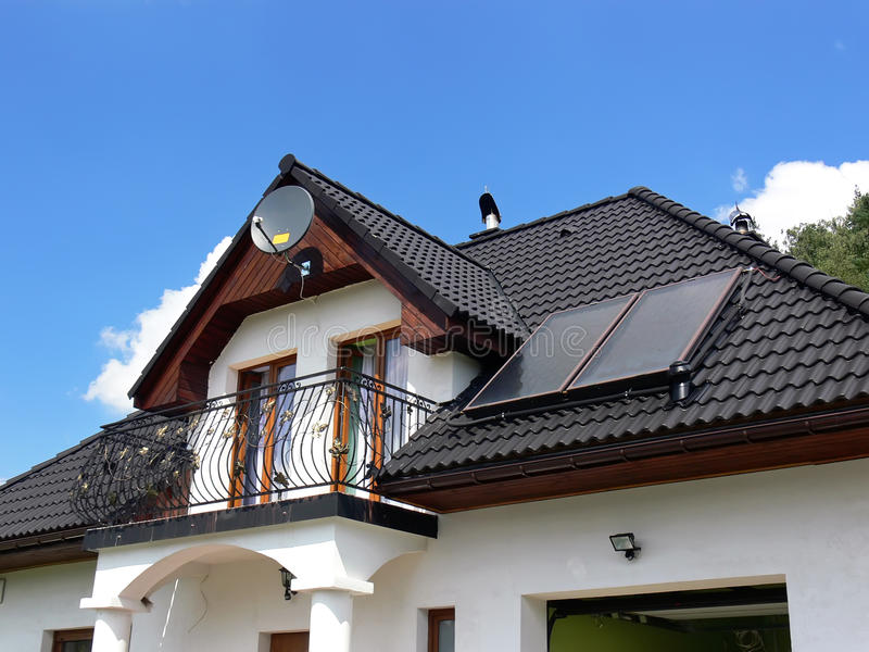 House with solar panels. New white house with with balcony and solar panels on the black roof royalty free stock photos