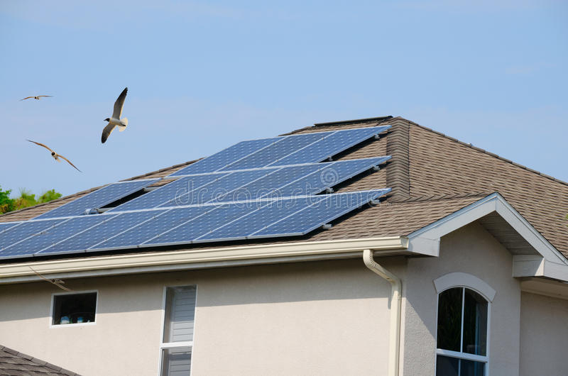 House with solar panels and flying birds royalty free stock photography