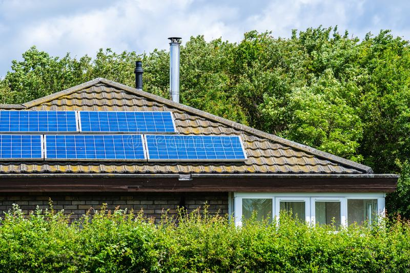 A house with a solar panels panels installed on the tile roof stock photography