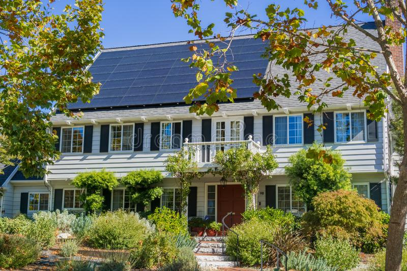 House with solar panels on the roof in a residential neighborhood of Oakland, in San Francisco bay on a sunny day, California royalty free stock images