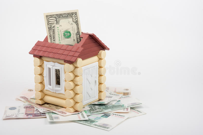 House stands on banknotes of Russian rubles, from the roof sticking out of ten US dollars banknote stock photography
