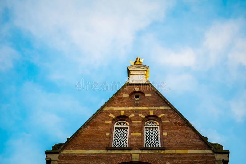 House with statue on top. Amsterdam house with angel statue on top stock photography