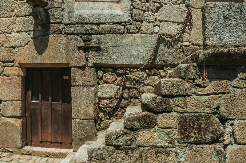 House with stone staircase and wooden door. Close-up of gothic house with stone staircase and wooden door on deserted alley, in a sunny day at Sortelha. One of royalty free stock image