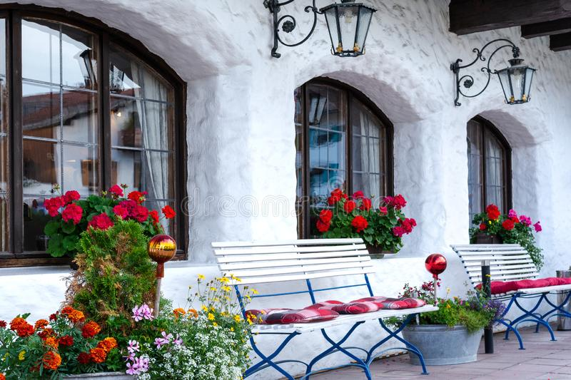 The house territory is decorated with white shops, flowers and forged lanterns.  stock photography