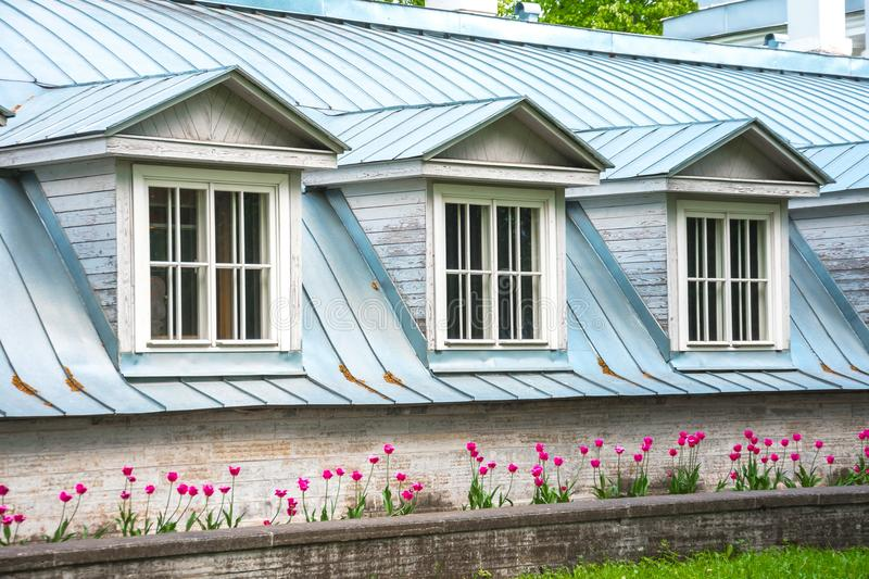 The house with three windows and roofs under them with a flower bed and lawns in front of the building in the yard. The house with three windows and roofs under royalty free stock images