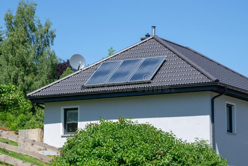 House with tiled roof and solar thermal power plant royalty free stock photography