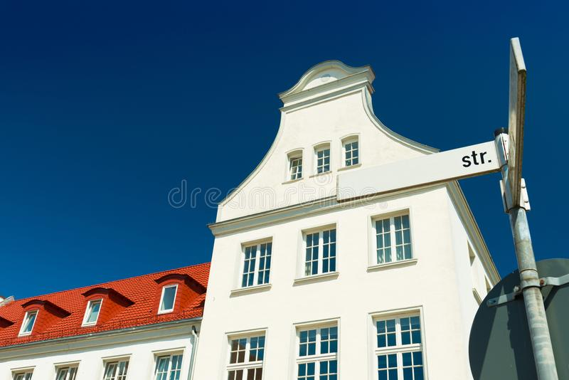 House in the traditional german-danish style. Street sign with direction pointers. House in the traditional german-danish style with blue sky on the background royalty free stock photography