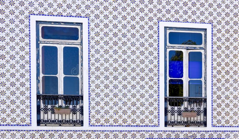 House with two windows decorated with traditional ceramic Portuguese tiles stock images