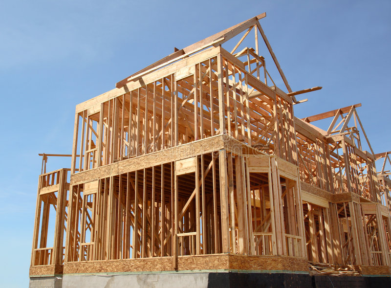House Under Construction. Sideview of a house is being built under construction in wooden frame skeleton royalty free stock photo