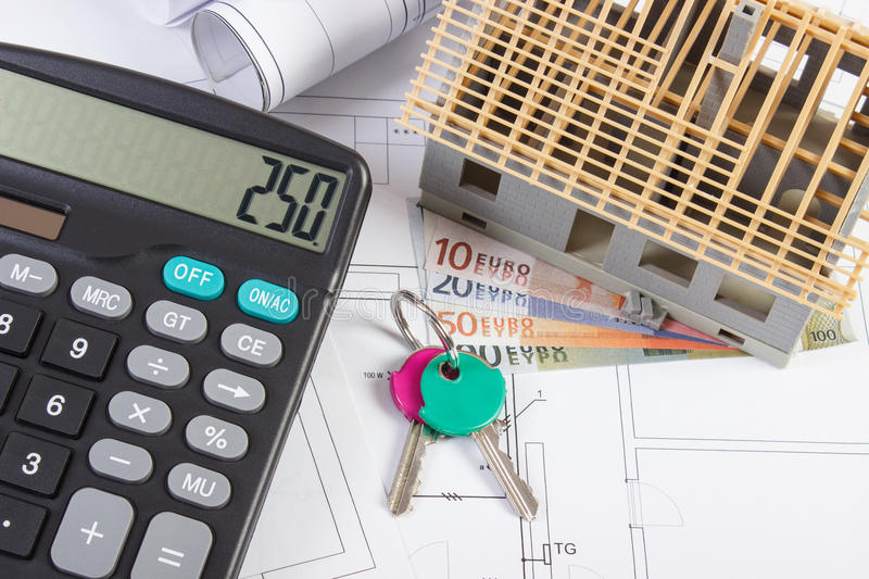 House under construction, keys, calculator, currencies euro and electrical drawings, concept of building home. Small house under construction, home keys royalty free stock images