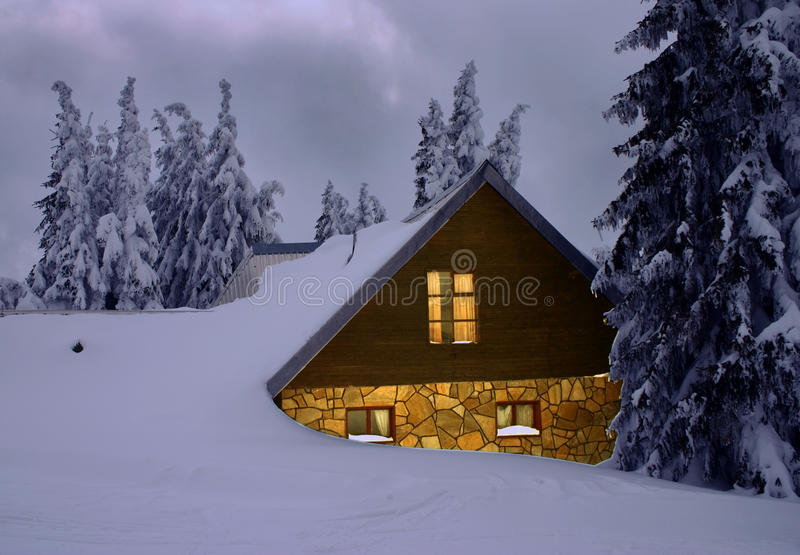 A house under snow. Small cozy cottage is nestled under the snow stock photography