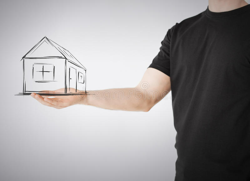 House on virtual screen in man hand. Real estate, technology and accomodation concept - picture of house on virtual screen in man hand royalty free stock photography