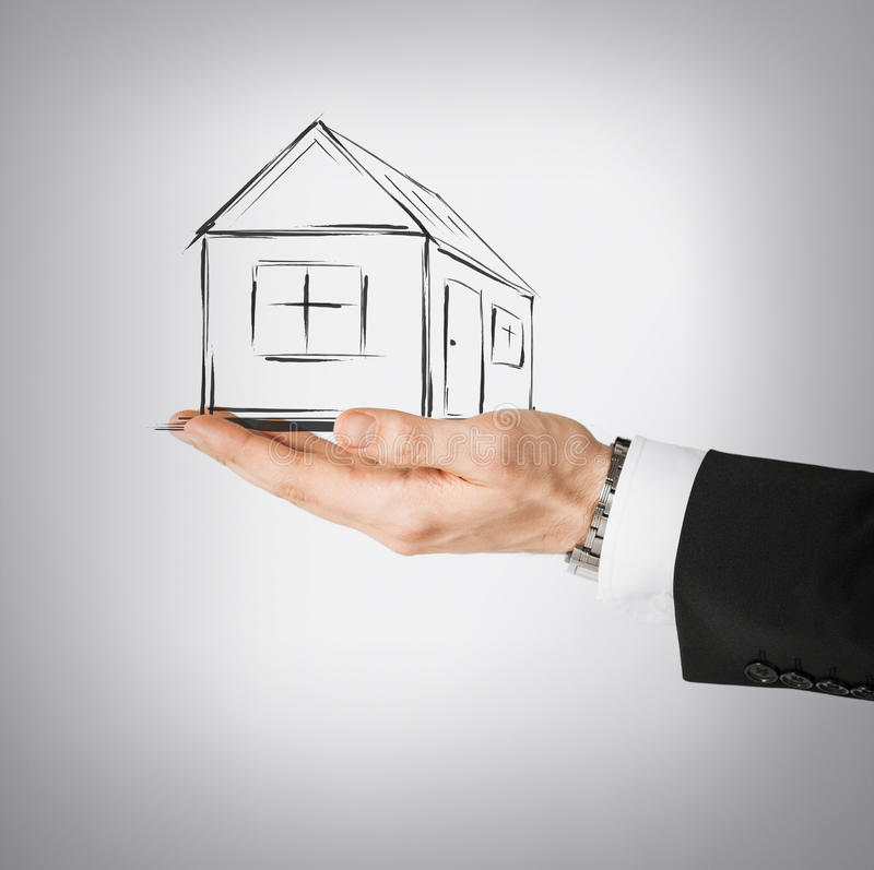 House on virtual screen in man hand. Real estate, technology and accomodation concept - picture of house on virtual screen in man hand stock photo
