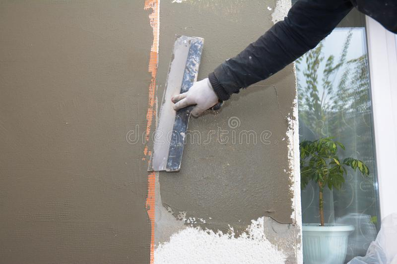 House wall renovation, insualtion with plastering layers,  reinforcment mesh, styrofoam insulation, finishing render, stucco. Contractor hand with trowel royalty free stock photos