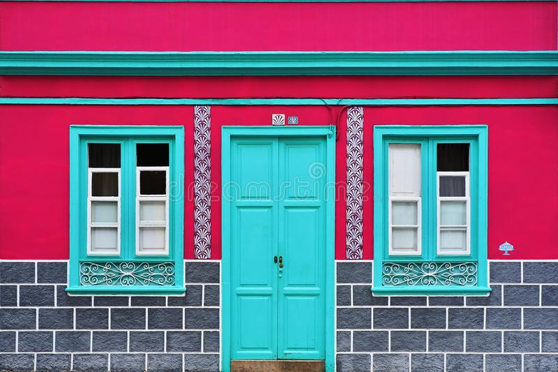 House wall in strong pink with neon green. Windows and door, as well as ice-gray blinds below, on tenerife in Puerto de la Cruz stock photography