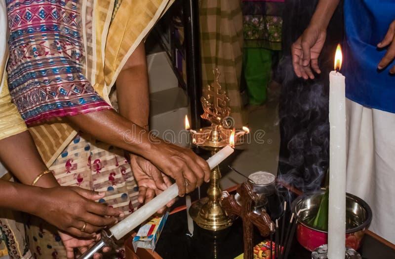 House warming rituals in Kerala Malankara Orthodox church - Lighting up Nilavilakku with candle. Kollam, Kerala, India - January 19, 2017: House warming rituals royalty free stock images
