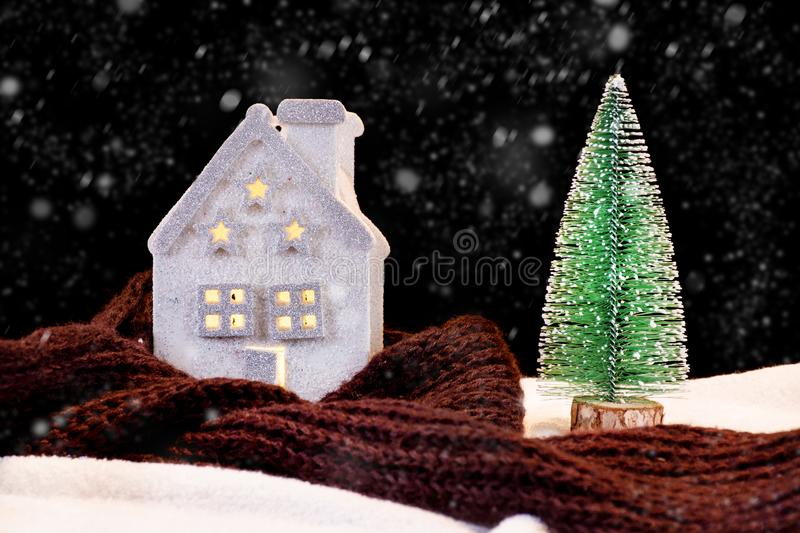 House and warming scarf around and green Christmas tree. Beautiful small Christmas house and warming scarf around and green Christmas tree in night winter season stock photography