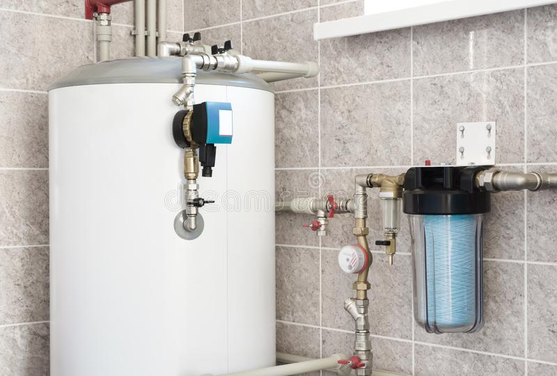 House water heating boiler with pump, ball valves and filters stock image