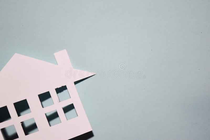 House of white paper showing a concept for home on blue background. royalty free stock photography