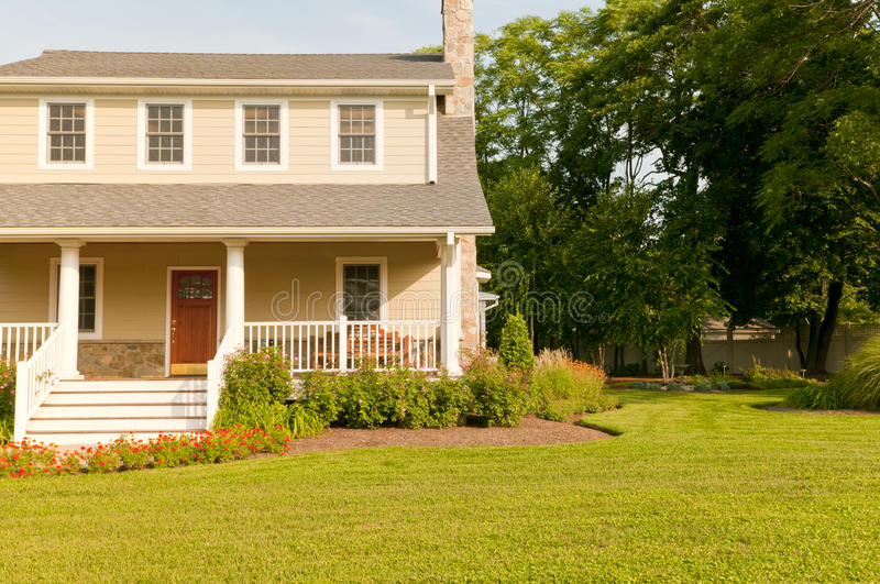 House with white porch. A view of a modest suburban house with a large white porch, green front lawn, flowers and landscaping stock photos